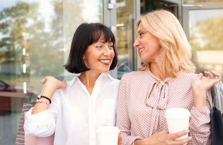 Photo pour Two mature women having fun while doing shopping and drinking coffee. Pastime concept of mature people - image libre de droit