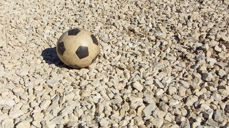 Childrens rubber soccer ball old. Background, sport equipment for outdoor fitness or beach soccer modern gravel texture. Playground of small dry stones texture of from quarry or mine.