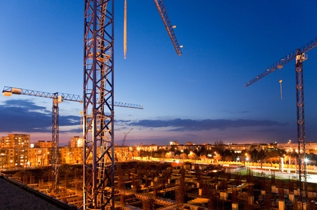 construction site with cranes at dusk
