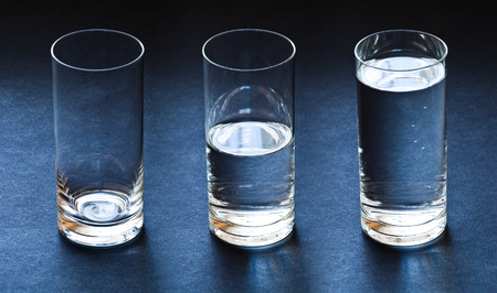 three glasses empty half and full with water on dark blue background