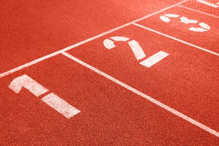 Close up of numbers on red running track.
