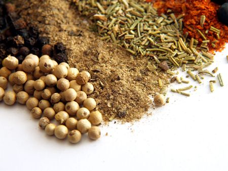 closeup of various colorful spices over white