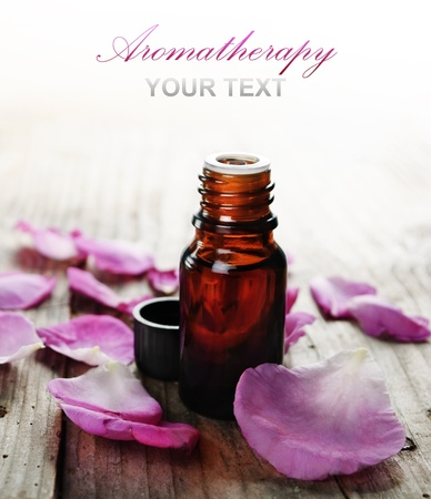 Essential oil with rose petals on wooden background
