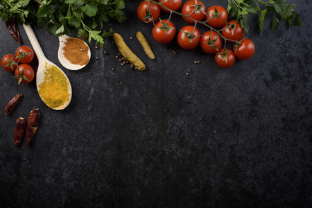 Food ingredients and various spices on black rustic background