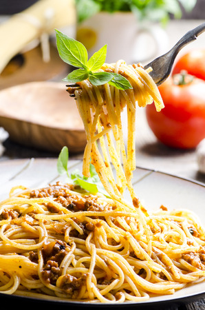 Foto de Closeup of italian spaghetti bolognese with basil serve on plate. Traditional homemade italian food recipe. Cooking and gastronomy concept. - Imagen libre de derechos
