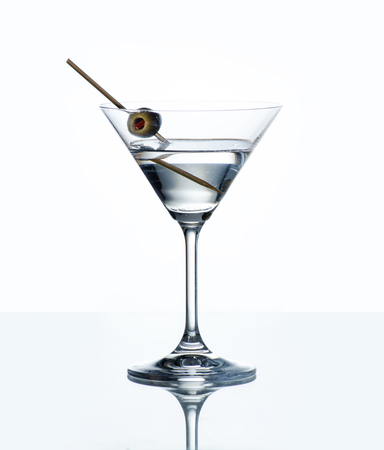 Photo pour Dry martini with green olive in cocktail glass over white background with reflection. Luxury alcohol drink on bar counter. - image libre de droit