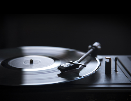 Retro gramophone vinyl player over black background with copyspace. Dj music and soundtrack album design.