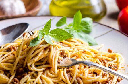 Photo pour Closeup of italian spaghetti bolognese with basil in fork. - image libre de droit