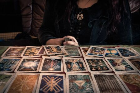 Photo for Spiritual wicca witch reading occult mystic old tarot cards laying on table for a magical pagan ritual psychic destiny reading - Concept of supernatural, witchcraft, destiny and mystical fortune-telling. - Royalty Free Image