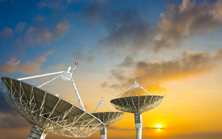Photo for Satellite dish receiving data signal for communication, on colorful sunset sky - Royalty Free Image