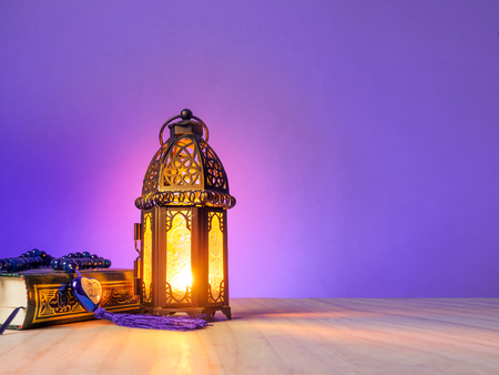 Photo for candle light of muslim style's lantern shining on arabic letters of the name of Muslim God Allah in heart shape with holy book Quran. - Royalty Free Image