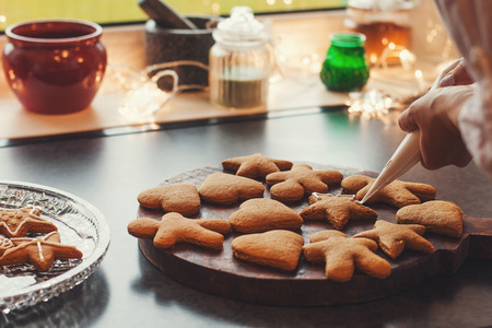 Girl decorates with glaze ginger cookies on her citchen.