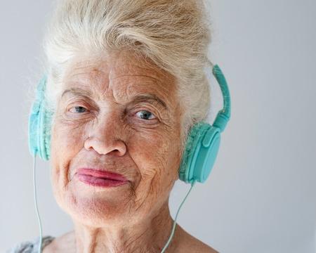 Portrait of smiling elderly woman wearing headphones looks at camera.