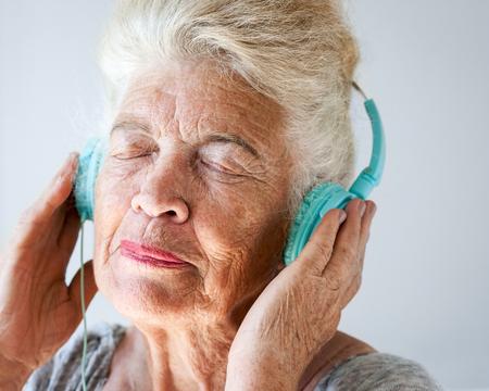 Portrait of elderly woman closed eyes wearing headphones.