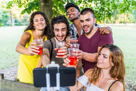 Photo for multiethnic group of millennial friends take a selfie while celebrating a birthday outdoors - Royalty Free Image