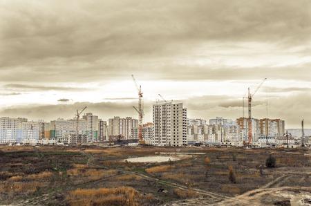 Photo pour View of cranes and new modern residential buildings on construction site - image libre de droit
