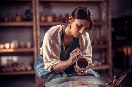 Charming potter female student works with clay on a potters wheel. Restoration of forgotten pottery traditions.