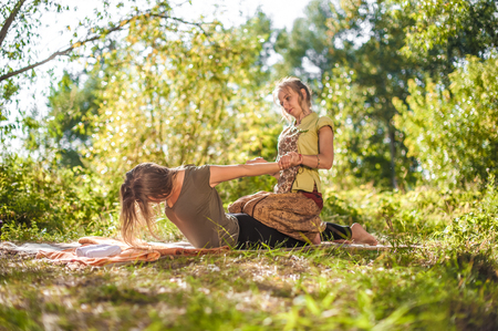 Massage therapist demonstrates refreshing massaging methods on the grass of the forest.