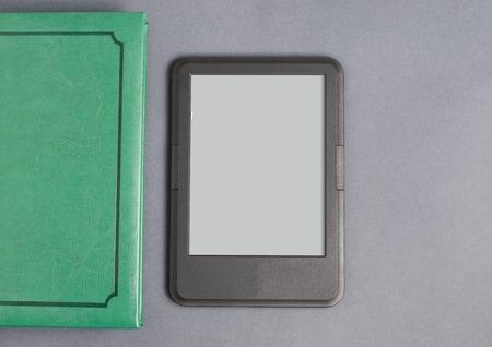 Foto de E-book reader and the green book. Gray background. Flat top view. Space for text - Imagen libre de derechos