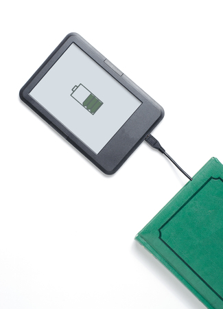 Foto de E-book reader and green book connected with cable. White background. Vertical photo. Space for text - Imagen libre de derechos