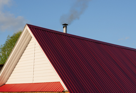 Foto per Tiled roof top with chimney with blue cloudy sky in background. Smoke raising from a chimney. Summer, noon. - Immagine Royalty Free
