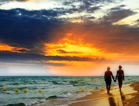 Foto de Lovers walk along the beach at sunset. - Imagen libre de derechos