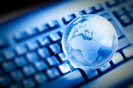 Glass globe over keyboard , global communication concept.