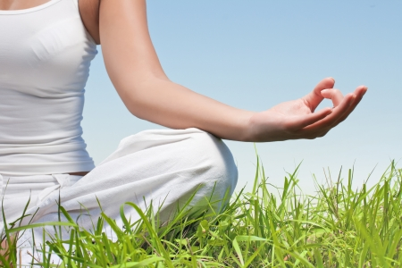 Closeup of woman hands in yoga meditation pose outdoors.