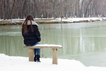 A lonely young woman sitting on a bench beside the lake, winter time.