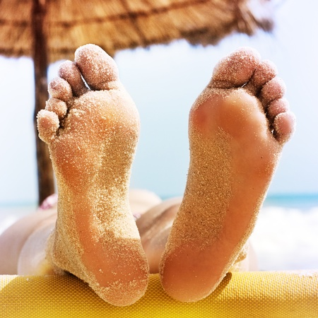 Closeup of woman feet with sand on the beach
