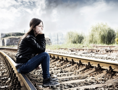 Lonely teenage girl sitting on railroad and thinking.
