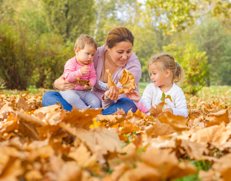 Photo pour Happy Family Enjoyment Beautiful Autumn Day Mother with two Daughters  in the park. Happiness Family carefree Relaxing fall season concept. - image libre de droit