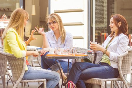 Three Young Women have Coffee Break Together in street cafe. Caucasian female relaxing on beautiful summer day in the city.