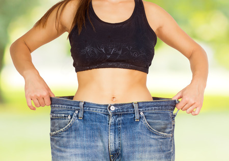 Slim Waist of Young Woman with perfect healthy thin body,showing her old jeans after successful diet over nature background.