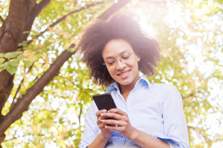 Beautiful Young Black Woman Using Phone In Nature. Outdoor Portrait, Wears Glasses , Looking At The Phone, Sunlight Flare In Background