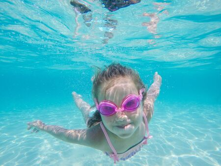 Photo pour Happy child underwater portrait - Little girl wearing swimming goggles dive and swim in the seawater - Summer vacation fun - image libre de droit