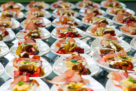 Photo pour Caterer puts the starter on many plates with vegetables and antipasti - image libre de droit