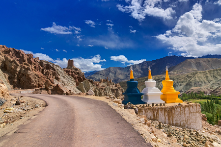 Three colourful buddhist religious stupas at Leh, Ladakh, Jammu and Kashmir, India. Religious symbols in landscape,  with himalayan mountain, road and blue sky.