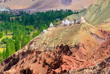 White buddhist religious stupas at Leh, Ladakh, Jammu and Kashmir, India. Religious symbols in landscape,  with himalayan mountain, green tress in background.
