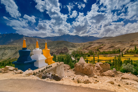 Three colourful buddhist religious stupas at Basgo, Leh, Ladakh, Jammu and Kashmir, India. Blue sky with clouds and Himalayan mountains in the background.