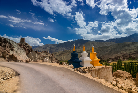 Three colourful buddhist religious stupas at Leh, Ladakh, Jammu and Kashmir, India. A road passing through. Shot under daylight with blue sky and white clouds in background.