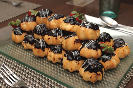 Eclair with hot chocolate fudge on food table