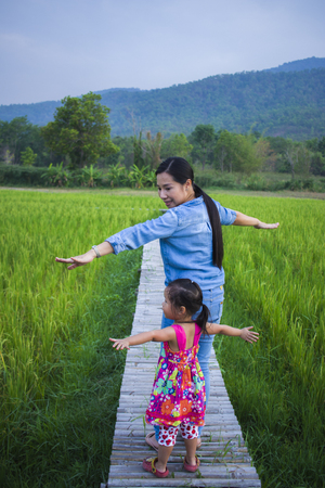 Photo pour Happy Mother and her child play outdoors having fun, Green  rice field back ground. High resolution image gallery. - image libre de droit