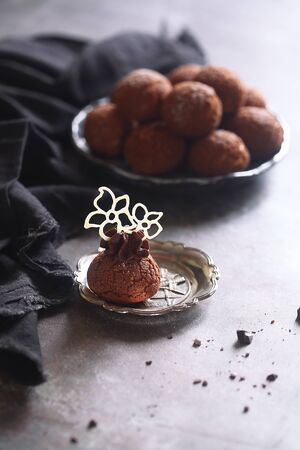 Chocolate Choux Pastry Puffs with Craquelin, powdered with icing sugar, on a plate, on gray background.