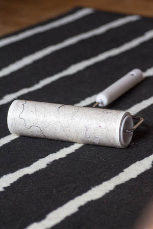 Dirty lint roller on a black and white carpet