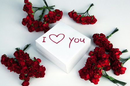 notebook with marker inscription I love you and artificial roses