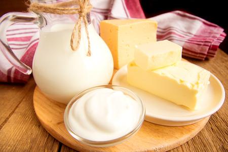 Photo pour Dairy products - milk, cheese, butter, sour cream over wooden table - image libre de droit