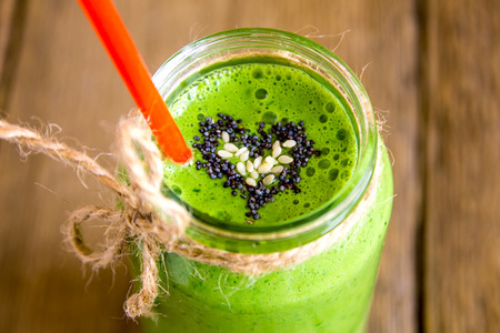 Green vegetable and herbs smoothie with heart of poppy and sesame seeds. Love for a healthy raw food concept.の写真素材