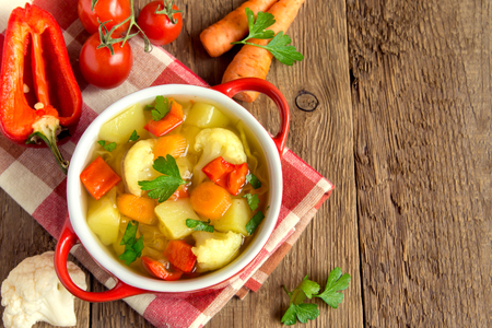 Vegetable soup with ingredients carrot cauliflower potato parsley pepper cabbage tomato over rustic wooden background with copy space