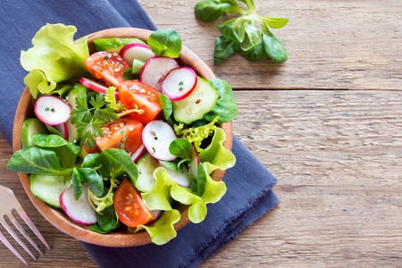 Foto de Fresh green spring vegetable salad with cucumber, radish, tomatoes and seeds in wooden bowl over rustic background with copy space - Imagen libre de derechos